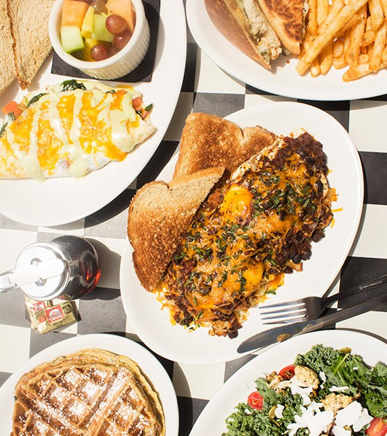 """An array of Kingside's food, including a spinach omelet, grilled chicken Cuban sandwich, the """"Kingside Slider,"""" waffled French toast and kale salad. - MABEL SUEN"""