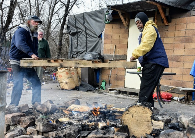 Robert Gibson (left) and Orlando Giles lift a pallet onto a fire at the East St. Louis camp. - DOYLE MURPHY