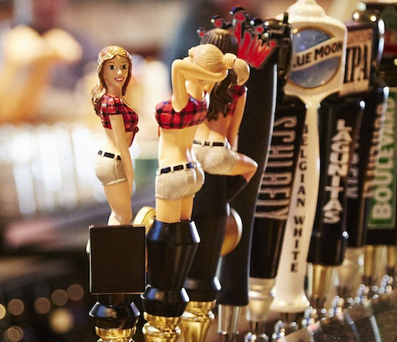 "The ""Twin Peaks girls"" decorate some of the bar's many taps. - PHOTO BY STEVE TRUESDELL"
