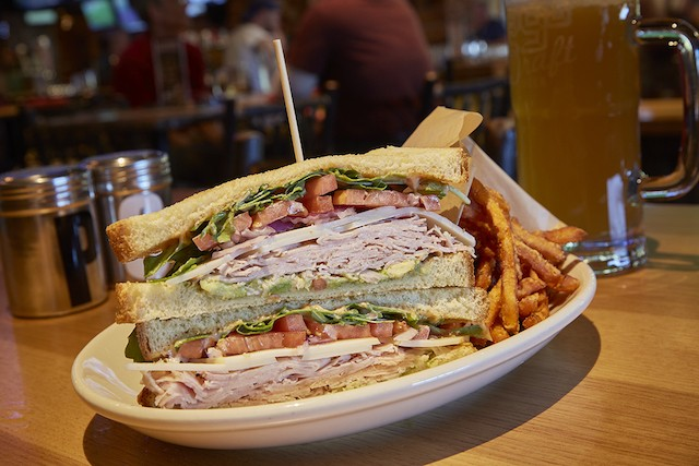 Sliced turkey sandwich on potato bread with Swiss cheese, avocado smash, arugula, tomato, red onions and mayo, served with sweet potato fries. - PHOTO BY STEVE TRUESDELL