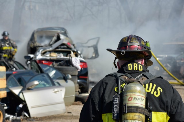 St. Louis firefighters work to put out cars in a salvage yard near Manchester Avenue. - DOYLE MURPHY