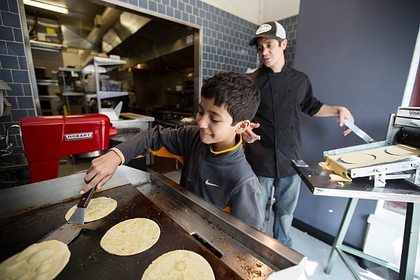 Mission Taco Chef-Owner Jason Tilford with his son, then 10, in the kitchen. The taco joint is great for date night — but also surprisingly accommodating to young families. - PHOTO BY JENNIFER SILVERBERG