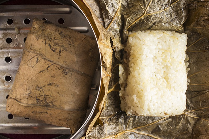 Sticky rice in lotus leaf: Sweet rice, Chinese sausage, pork, egg and shiitake mushrooms wrapped in a large tea leaf and steamed. - PHOTO BY MABEL SUEN