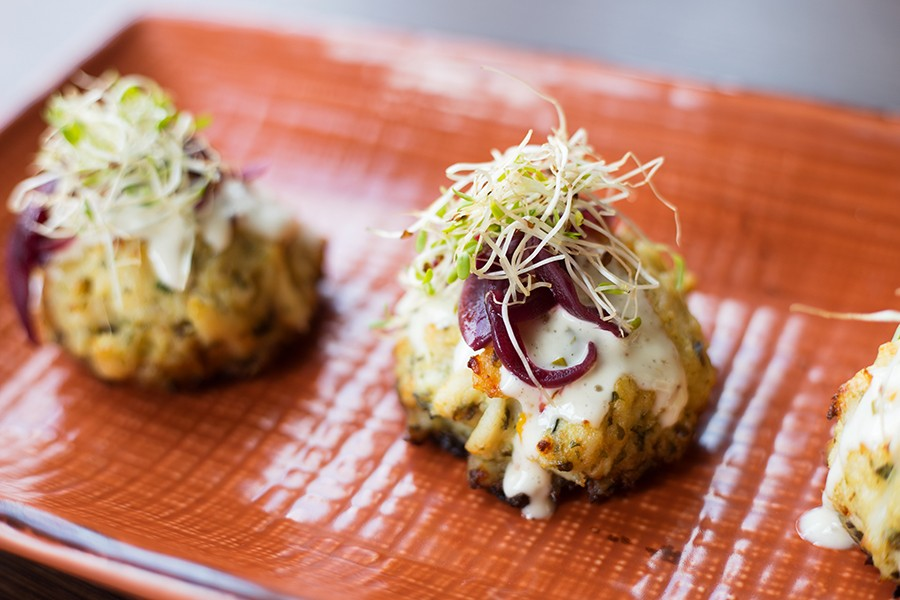 The crab cakes are made with a shockingly generous amount of crab and served with lemon aioli and pickled red onion. - MABEL SUEN