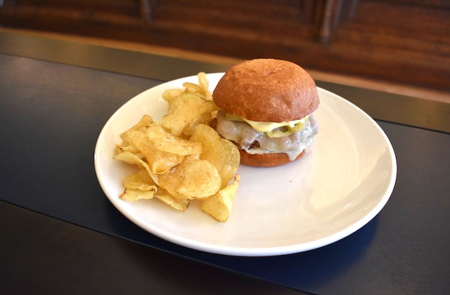 The braised brisket sandwich with provolone, horseradish, Dijon and pickled banana peppers with a side of chips. - LIZ MILLER