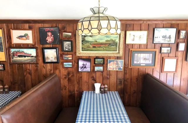 The dining room features wood paneling, retro framed artwork and vintage stained glass light fixtures. - LIZ MILLER