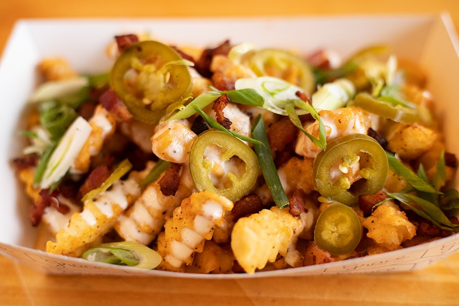 Garlic loaded fries with queso, bacon, pickled jalapeño, buttermilk-lime dressing and green onion. - MABEL SUEN