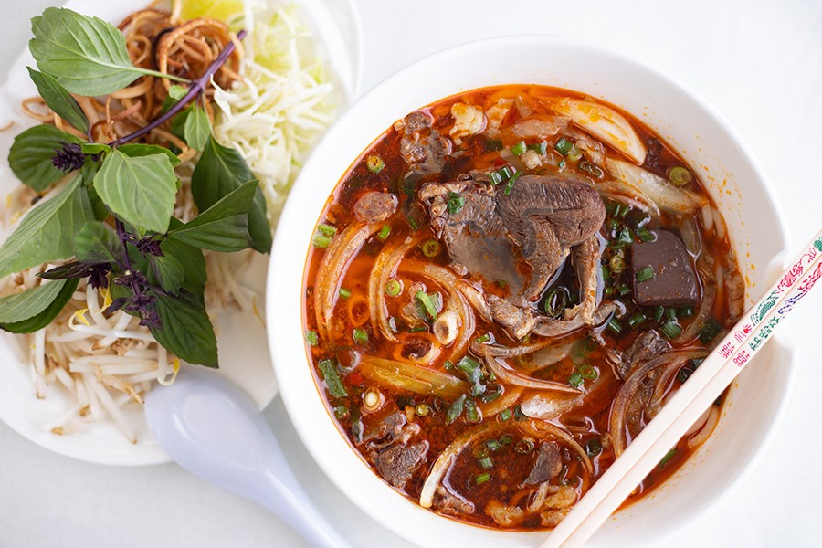 Bún bò huế with noodles, pork patty, pork feet and beef shank and a side of fresh herbs and bean sprouts to incorporate in the soup. - MABEL SUEN