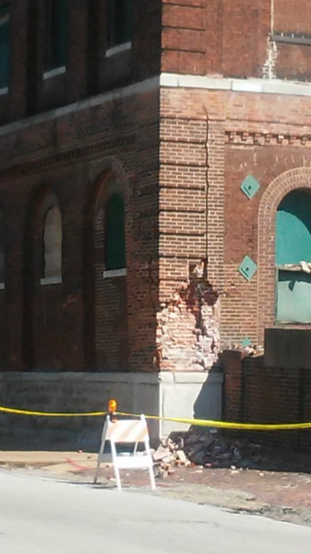A crack runs up the side, and bricks lie on the street two days before the partial building collapse. - AARON P. BURY