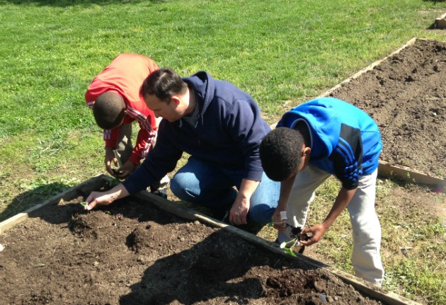 Lift for Life Executive Director Joe Miller and two young members plant cucumbers at the gym's garden. - PHOTO BY DOYLE MURPHY