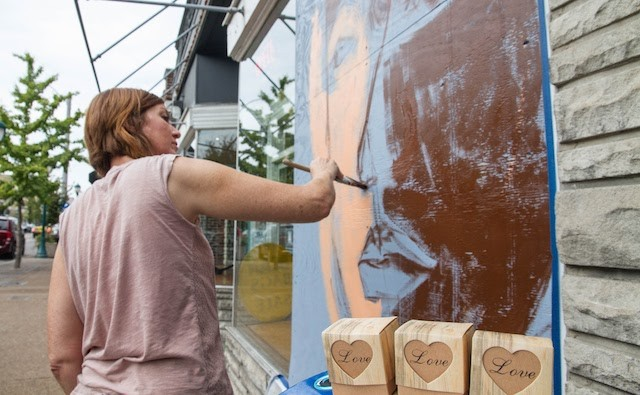 Artist Marnie Claunch paints a mural in the storefront just west of Insomnia Cookies. - COURTESY OF PAINTING FOR PEACE IN FERGUSON, A CHILDREN'S BOOK