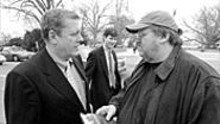 Michael Moore (right) talks with Congressman John - Tanner on Capitol Hill. Moore spent the day - approaching pro-war members of Congress to recruit - their children to fight in Iraq.