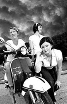 MARK  GILLILAND - Queens of the road: scooterists Shirley Hurst, Jen - O'Hair and Jen Curtis with a 1980 Vespa.
