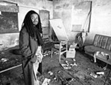 JENNIFER  SILVERBERG - Reverend Osagyefo Uhuru Sekou stands inside a garage around the corner from where he lived as a kid
