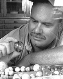 WM.  STAGE - Jim Meiners and some 19th-century marbles recovered from old city outhouses.