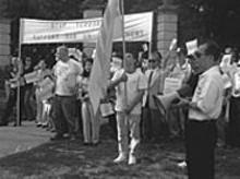 "D.J.  WILSON - Lan Tran (with bullhorn): ""We support President Bush."""