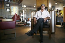 JAMIE PEACHY - Rick Orr relaxes among mid-century treasures, some from his own stash, at Red Modern Furniture in Phoenix.