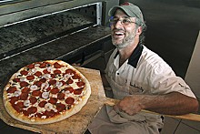 KRISTAN LIEB - Shrimply delicious: Onesto's Seth Berkowitz pulls a pizza with shrimp from the oven.