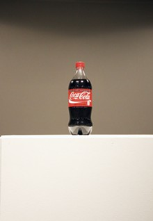 Installation view of Helmut Smits' oil filled Coca-Cola bottle.