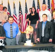 STEPHEN LEMONS - Arizona Governor Jan Brewer signing SB 1070 into law.