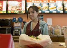 JENNIFER  SILVERBERG - Ba Le employee Tuyen Kieu serves a freshly made banh - mi.
