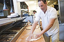 JENNIFER SILVERBERG - Owner John Racanelli says one of the secrets to his pizza is working it on the board.