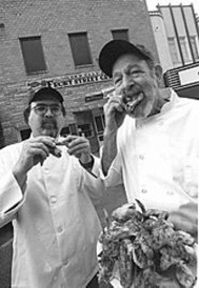JENNIFER  SILVERBERG - Front Street Grille owners Joe Sutterer (left) and Dennis Connolly munch hot wings.