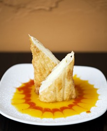 Xangos - cheesecake wrapped in a pastry tortilla and fried until flaky, on a bed of mango sauce dusted with powdered sugar.