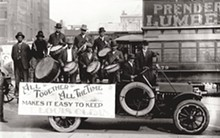 """MISSOURI HISTORICAL SOCIETY - An African American drumming group perform on the back of a truck carrying a banner that reads """"All Together All the Time Makes It Easy to Keep St. Louis Clean"""" on Market Street. Photograph, 1912."""