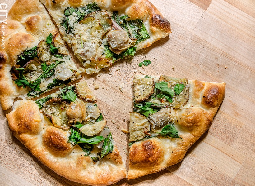 A pizza with little-neck clams, Swiss chard, roasted potatoes, and shaved garlic from Aunt Rosie's. - PHOTO BY MARK CHAMBERLIN