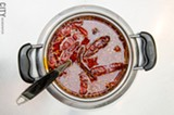 PHOTO BY MARK CHAMBERLIN - A pot of spicy broth with garlic, Szechuan peppercorn, and spices from Yummy Garden Hot Pot.
