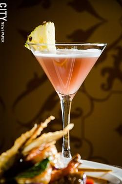 A Vietnamese Kiss cocktail made with mango vodka, pineapple juice, Chambord and champagne at Papaya. - PHOTO BY MARK CHAMBERLIN