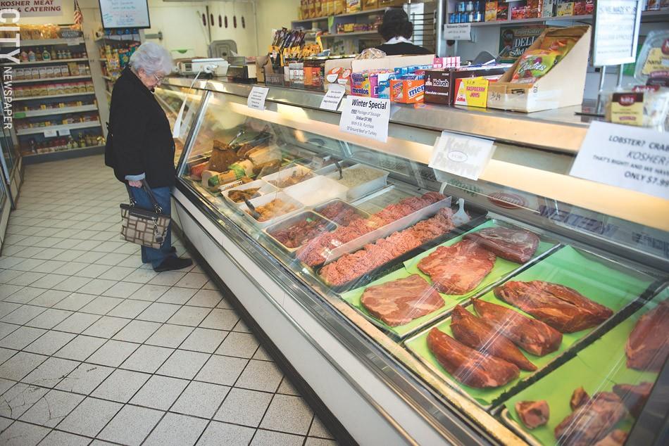 A woman surveys the display case at Lipman's Kosher Market. - PHOTO BY THOMAS DOOLEY