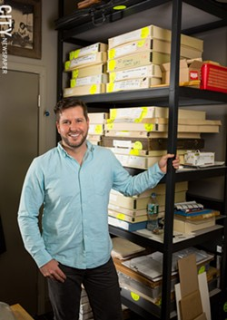 Adam Werth, in front of the boxed print collection of the Print Club of Rochester. - PHOTO BY JOHN SCHLIA