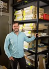 Adam Werth, in front of the boxed print collection of the Print Club of Rochester.