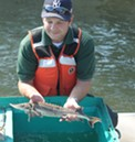 DEC staffer Dan Mulhall holds up a 2-year-old sturgeon. - PHOTO BY JEREMY MOULE