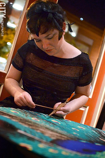 Artist Katie Jo Suddab works on a peacock sand mandala in Geva's cafe. - PHOTO BY MATT DETURCK