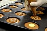 Baran fills molds with chocolate. - PHOTO BY MATT DETURCK