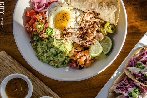 carnitas plate: roasted pork, tortillas, beans, salsa, gremolata, queso crema, guacamole, pickled vegetables, and a fried egg. - PHOTO BY MARK CHAMBERLIN