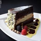 Chocolate Broadway cake with layers of chocolate cake, ganache, and vanilla cheesecake from Tournedos Steakhouse. - PHOTO BY MATT DETURCK