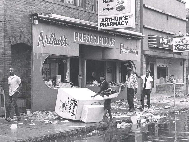 Citizens attempt to cross a debris-laden sidewalk on Joseph Avenue at Arthur's Pharmacy and Blake's Barber Shop. - PHOTO COURTESY THE CITY OF ROCHESTER, ROCHESTER, NEW YORK.