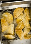 Fresh empanadas, seen here frying in the kitchen.