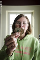 PHOTO BY MARK CHAMBERLIN - Margaret O'Neill holding tokens in the market office.