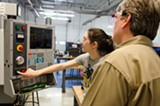 PHOTO BY MARK CHAMBERLIN - Meghan Davey sets up and operates a CNC machine at Monroe Community College's Applied Technologies Center.