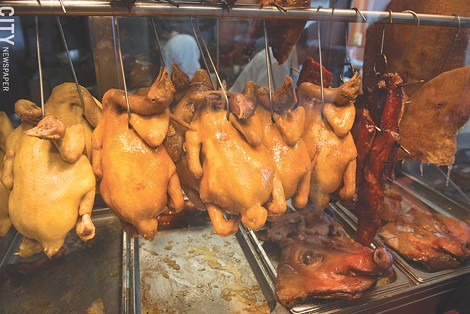 Poultry and pork hang in the meat counter at Asia Food Market. - PHOTO BY THOMAS DOOLEY