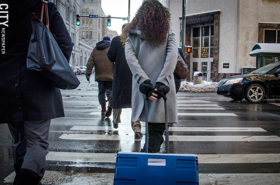 Public Defender Fabienne Santacroce walks to court, pulling a cart full of case files. - PHOTO BY MARK CHAMBERLIN
