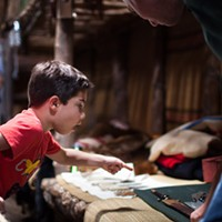 [ Slideshow ] Ganandogan Dance & Music Festival Seven year old Willem Oliveiri of Rochester leans over to ask Ganondagan docent Jordan Dube about a large knife while inside the longhouse. PHOTO BY MATT BURKHARTT