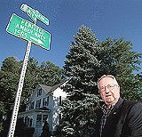 KURT BROWNELL - Stranded - by the county? Penfield town supervisor Channing Philbrick standing alongside a - county road that his town may have to pay to maintain.