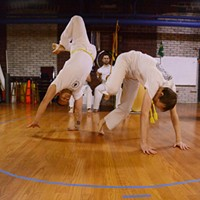 Capoeira at Com Expressao Students sparring while others clap, sing, and play instruments. PHOTO BY LARISSA COE