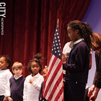 Mayor Lovely Warren's Inauguration Ceremony Taylor Granison and her classmates lead the auditorium in the Pledge of Allegiance. PHOTO BY JOHN SCHLIA